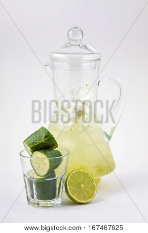 glass decanter cucumbers with lime juice and ice on a white background