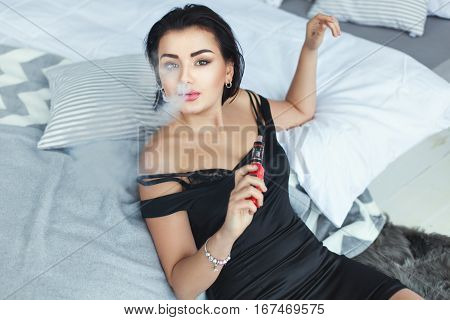 Woman sexy smoke in the room near the bed.