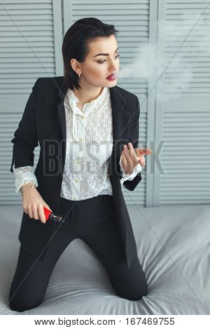Woman in a business suit smokes electronic cigarette.