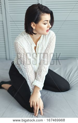 Woman in diaphanous shirt on the bed in the bedroom.