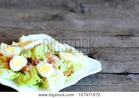 Chinese cabbage salad with canned tuna and quail eggs dressing with olive oil and lemon juice. Cabbage salad on plate on wooden background with copy space for text. Closeup