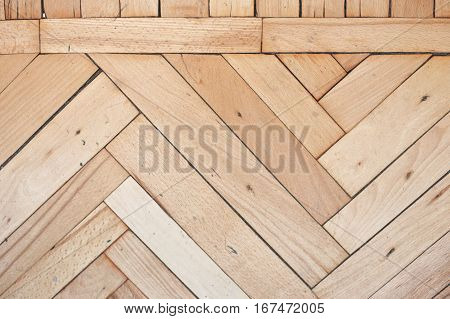 Close view on rich texture of old brushed and distressed wooden parquet floor made from many racks in herringbone and simple row pattern on top, abstract background image