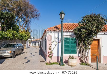 Beautiful typical rebuilt portuguese house in a village called cascais. with a pink frame in a sone made street surrounded by a garden and under the clear blue sky.