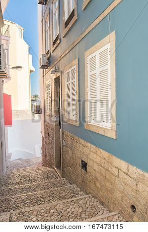 Stairs made of portuguese sidewalk rocks leading a way down to the entrance of a beautiful blue house with white metal shutters. Blue sky in the background.