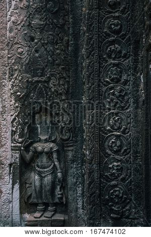 Devata sculpture without head in Ta Prohm temple at Angkor complex, Siem Reap, Cambodia