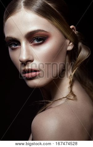 Beautiful fashion woman with creative make-up and hairstyle. The beauty of the face. Photos shot in the studio.
