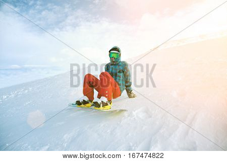 Unrecognizable beginner snowboarder girl wears her google mask and bright clothes, sits alone at top of ski slope in sun rays, ready to stand up and ride down