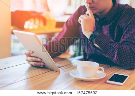 Young Asian Handsome Businessman Concentrated While Reading His Tablet