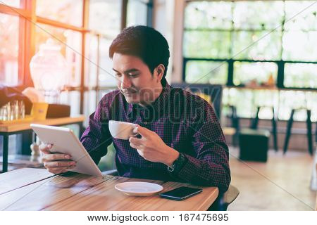 Young Asian Handsome Businessman Smiling While Reading His Tablet