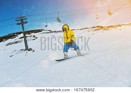 Man rides his snowboard on ski slope in winter mountains, in front of skilift ski resort