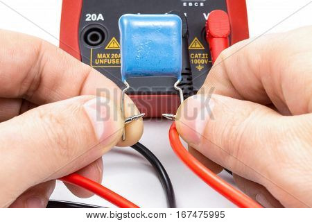 Testing capacitor with multimeter on a white background
