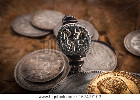 medieval silver ring with gilding against the background of old coins from precious metals and dry leaves