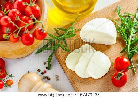 Sliced mozzarella tomatoes and arugula on table