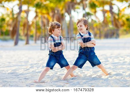 Two little kids boys having fun on tropical beach, happy best friends playing, friendship concept. Siblings brothes in family look with palms on background. Miami Florida USA
