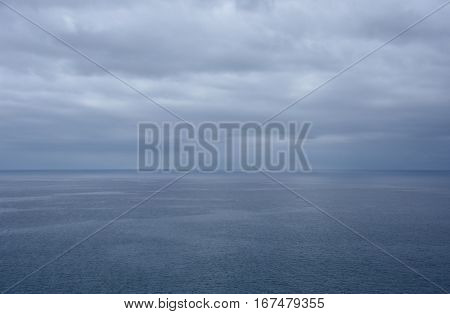 Gushing sea on a cloudy day. Horizontal view of dramatic overcast sky and sea. Fifty shades of blue.