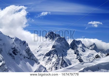 Winter mountains with snow cornice and blue sky with clouds in nice sun day. Caucasus Mountains region Dombay. View from the top of mount Musa Achitara.