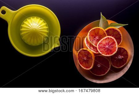 red sicilian oranges and squeezer on black background