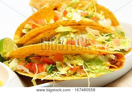 Two Beef tacos with lettuce, cheese, tomato, onion.