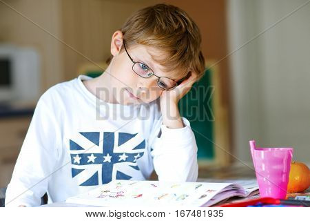 Portrait of frustrated school kid boy with glasses at home making homework. Little child writing with colorful pencils, indoors. Elementary school and education.