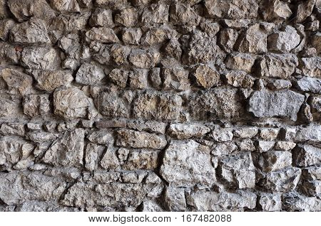 Stone wall pattern / texture - stacked rocks / blocks with varying size and shape, resembling the wall of an old and ancient building like a castle or fortress.