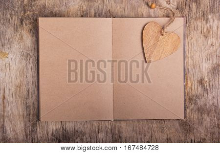 Open book with blank pages and a bookmark made of wood. Wooden heart. Personal diary. Valentine's Day. Copy space