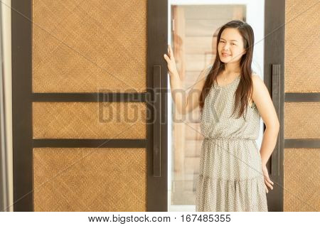 Woman posing with boutique wooden doors .