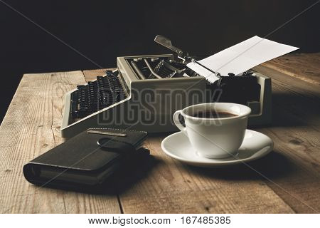 Old typewriter on a wooden table with blank paper