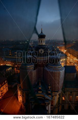 Restoration of the Cathedral of Vladimir  Icon of Our Lady in Saint- Petersburg.  Vladimirsky Cathedral in the construction staging.  The Cathedral against the background of the evening city. Top view of the Cathedral from the bell tower through the const
