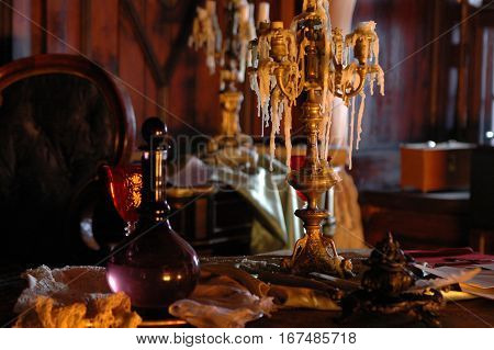 Mock-up of the candlestick of the times of the 18-19 th centuries in the northern capital of Russia. Mock-up of the 18-19 th century interior. Decoration element of the interior- the candlestick with candles and wax remains. The candlestick in the rich an