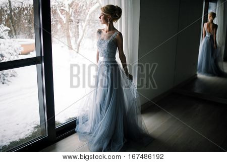 Bride standing in front of big window and looking to snowy garden. Her figure is reflected in large mirror.