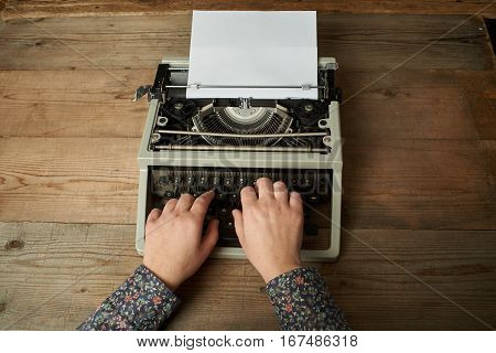 Woman is writing on an old typewriter.