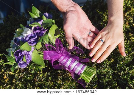Newlyweds with wedding rings closeup. Couple place their hands on bouquet.