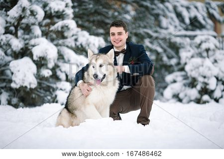 Groom in winter with dog malamute sitting in snow. He hugging dog and smiling.