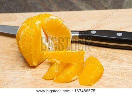Segmenting and orange Orange segments cut on a wooden board