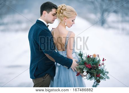 Bride and groom among snowy landscape. Bride and groom are standing and hugging. View from back. Winter wedding outdoors.
