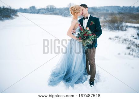 Bride and groom are kissing among snowy landscape. Bride and groom are standing kissing and hugging. Winter wedding outdoors.