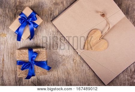 Open notebook with blank pages, valentine made of wood and boxes with gifts. Gift boxes with blue ribbon on the old wooden background. The concept for valentine's day. Copy space.