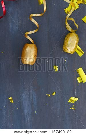 Carnaval festive golden curling paper with copy space on dark wooden background