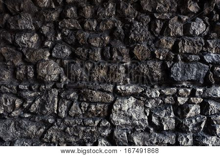 Dark rock wall made of irregular stone blocks with rough and uneven surface, creating a structured texture or pattern for backgrounds.