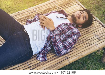 Young Man Take Nap On Bamboo Bed Or Seat