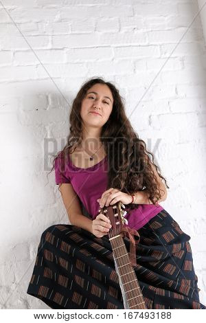 Young woman with guitar in long skirt. Brick wall background.