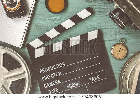 Clapperboard and a film reel a stop watch a notebook and a lens on the table