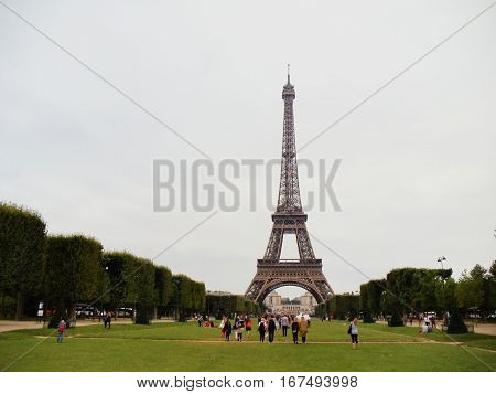 Eiffel tower and Champ de Mars central perspective in Paris, France. Famous tourist destination in Europe. Clear white blue sky empty background.