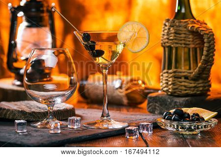 Martini cocktail and empty brandy snifter on bar counter next to fireplace