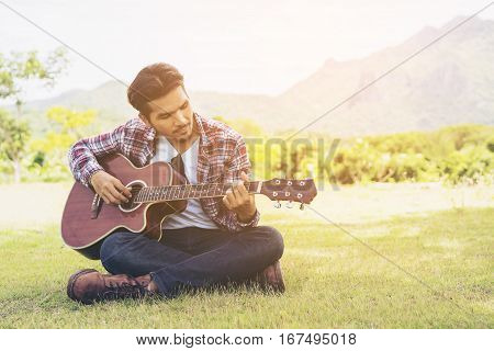 Handsome Man Playing Guitar On Green Grass