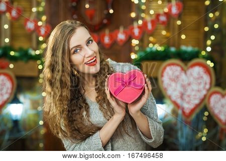 Attractive woman with a box in the form of heart looking at the camera and smiling. Valentine's Day Decorations