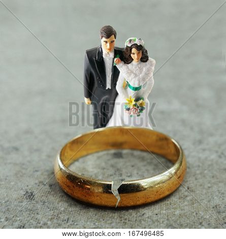 Bride and Groom figures behind a cracked gold wedding ring -- divorce or infidelity concept