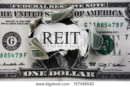 Torn dollar with REIT (Real Estate Investment Trust) paper message