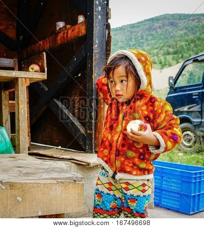 Tibetan Girl Playing At The Local Market