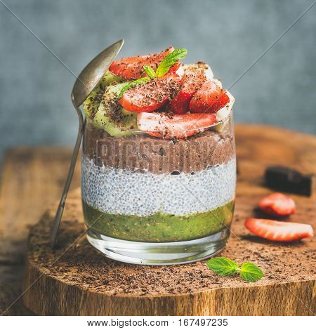 Healthy breakfast. Matcha, almond milk, cocoa chia seed pudding with fresh fruit, berries, mint, chocolate in glass over wooden board, grey wall background, selective focus, square crop. Detox concept